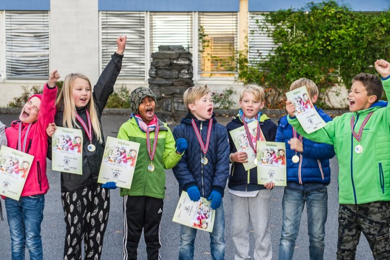 fornøyde elever i skolegården med diplom